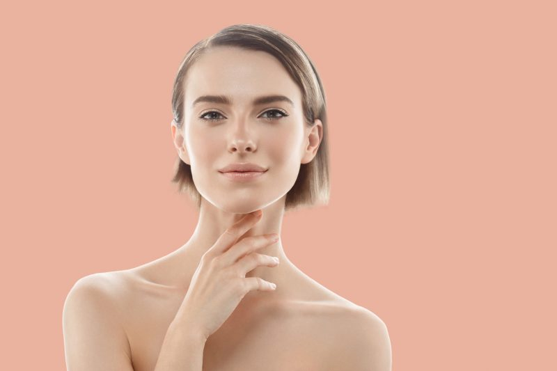 Young beautiful woman skin care concept portrait with hand touching skin face.